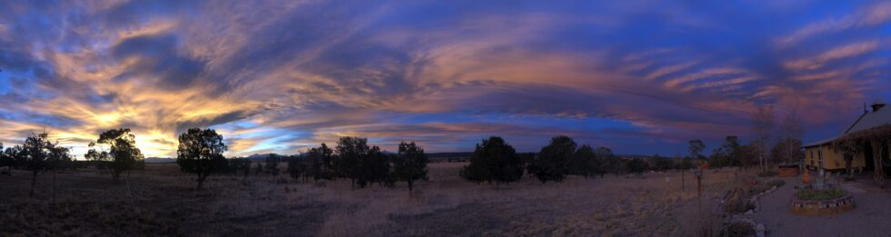 A panoramic view of fields and trees during a sunset